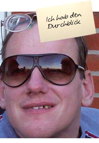 """Ein Mann mit einer Sonnenbrille auf der Nase und der richtigen Brille auf der Stirn blickt in die Kamera. Auf einem Zettel oben im Bild steht: """"Ich hab den Durchblick"""""""