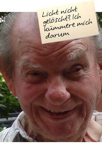 """Ein alter Herr lächelt in die Kamera. Auf einem Zettel oben im Bild steht: """"Licht nicht gelöscht? Ich kümmere mich darum"""""""