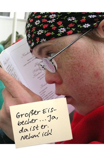 """Ein Mädchen liest eine Eiskarte und hält sie ganz dicht an die Augen. Auf einem Zettel oben im Bild steht: """" Großer Eisbecher ... Ja, da ist er. Nehm' ich!"""""""