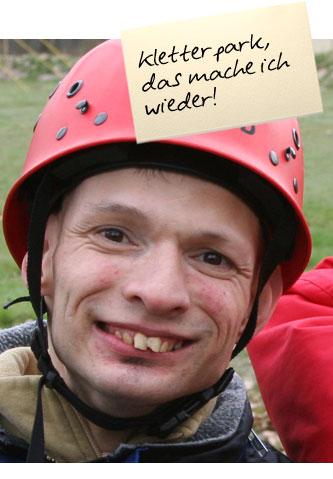 """Ein Mann mit einem roten Helm lächelt in die Kamera. Auf einem Zettel oben im Bild steht: """"Kletterpark, das mache ich wieder!"""""""