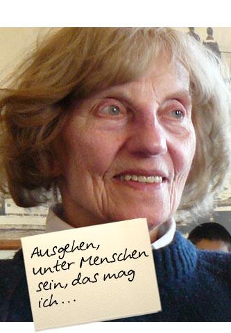 """Eine alte Dame sitzt vergnügt im Café. Auf einem Zettel oben im Bild steht: """"Ausgehen, unter Menschen sein, das mag ich ..."""""""